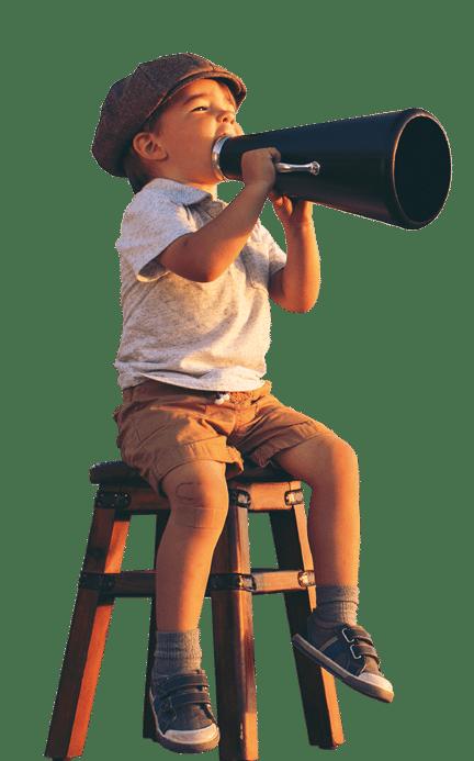 enfant sur un tabouret avec un haut parleur