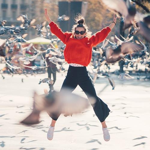 femme qui saute avec des oiseaux